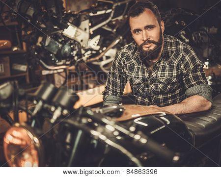 Mechanic building vintage style cafe-racer motorcycle  in custom garage