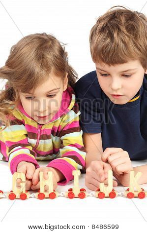 Little Boy And Girl Playing With Wooden Railway, Lying On Floor, Half Body, Isolated On White
