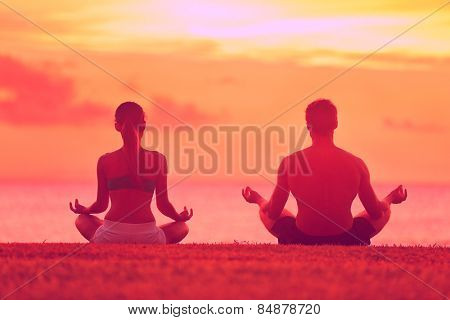 Meditation yoga couple meditating at serene beach sunset. Girl and man relaxing in lotus pose in calm zen moment in the ocean during yoga holiday class at resort retreat.