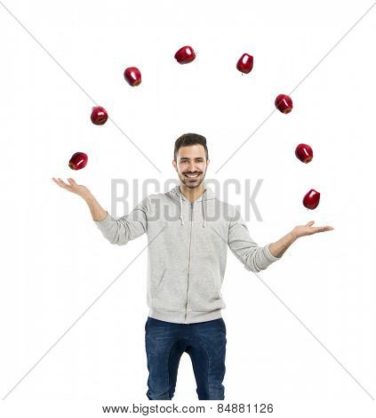 Happy young man juggling with apples on a white background