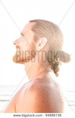 Happy man with his long hair tied in a ponytail enjoying the hot summer sunshine on a tropical beach looking up into the bright flare of the sun with a joyful spiritual smile, profile view