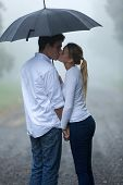 boyfriend and girlfriend kissing under umbrella in the rain poster