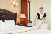 Hotel service. female housekeeping worker maid making bed with bedclothes at inn room poster