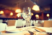 Served dinner table in a restaurant. Restaurant interior. Cozy restaurant table setting. Defocused background poster