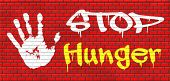 stop hunger suffering malnutrition starvation and famine caused by food scarcity undernourished bad harvest aid graffiti on red brick wall, text and hand poster