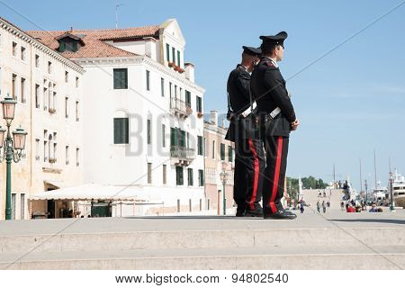 Two Carabinieri On Steps Near Venice Waterfront.