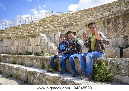 View of smiling boys sitting in the Roman Theater of Jerash, Jordan