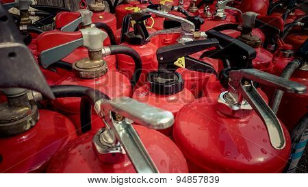 Lot Used Fire Extinguishers As Background