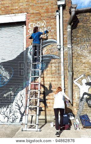 Graffiti artists paints the building wall