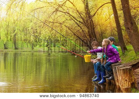 Happy kids fishing together near beautiful pond