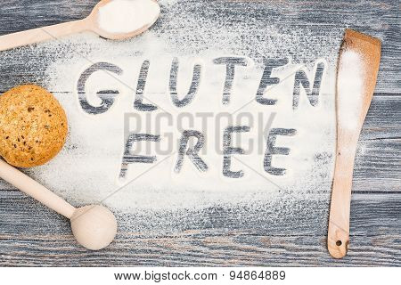 Gluten Free Word Written On Flour And Wooden Table.