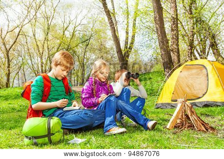 Happy children resting near the wooden bonfire
