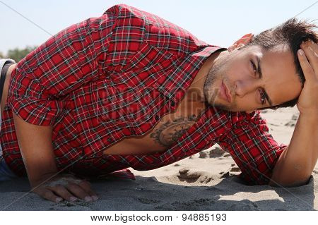 handsome male lying on the sand