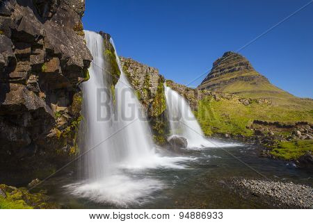 At The Bottom Of Kirkjufellsfoss Waterfall With Kirkjufell Mountain In The Background