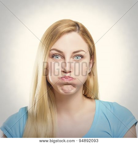 Portrait of a beautiful young blonde woman making pout. Toned photo. poster