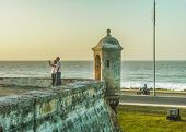 CARTAGENA COLOMBIA DECEMBER - 2014 - Couple taking a selfie photo colonial spanish fort with caribbean sea at background in Cartagena the most famous watering place of Colombia. poster