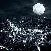Futuristic night aerial view panorama of Bangkok skyline at full moon night under dramatic cloudy sky. Thailand poster
