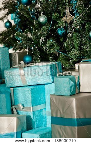 Christmas tree decorated with blue and silver Christmas decorations and wrapped gifts