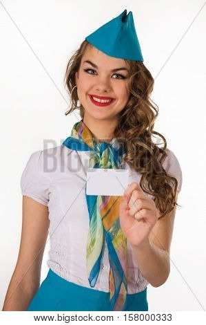 The young beautiful stewardess holds a card on a white background