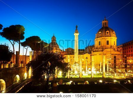 Forum - Roman ruins with column of Trajan in Rome illuminated at night, Italy, toned