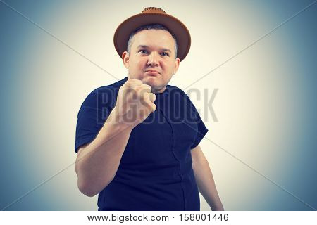 Gangster in hat angry man holding fists against. Isolated white background
