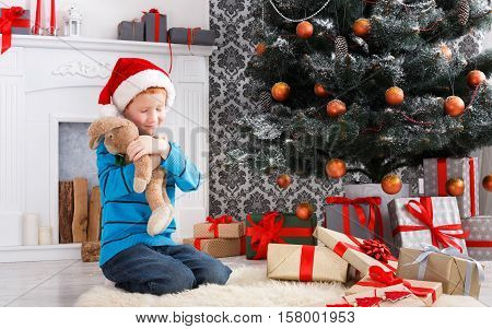 Cute happy boy in santa hat hug toy rabbit, christmas present on holiday morning in beautiful room. Male child got Xmas gift near decorated fir tree and fireplace. Winter holidays concept