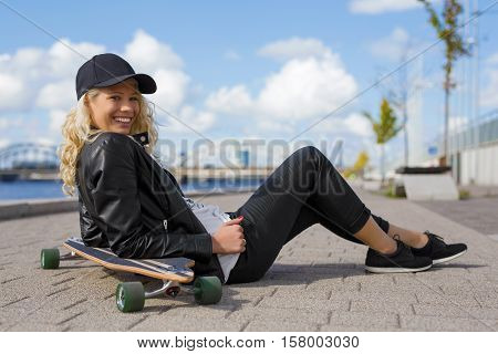 Happy woman with longboard sitting on the ground