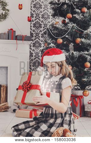 Beautiful happy girl in santa hat unwrap magic shine christmas present on holiday morning in beautiful room. Female child open Xmas gift near decorated fir tree and fireplace. Winter holidays concept