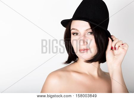 Closeup portrait of beautiful sexy young woman in black hat, posing.