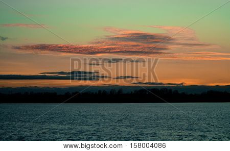 sunset in autumn in November, a bright yellow, brown and black colors, the sun behind horizon, clouds, bright orange heavy different sizes, the dark water of the pond,azure hue
