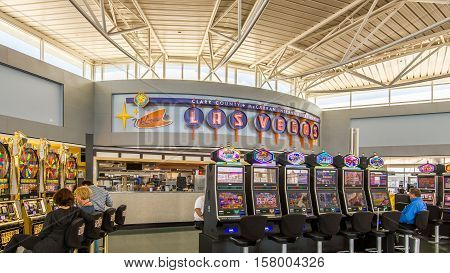 LAS VEGAS NV/USA - NOVEMBER 7 2016: People playing slot machines at McCarran International Airport terminal below a