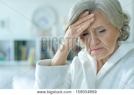 Portrait of sad senior woman with hand on her forehead