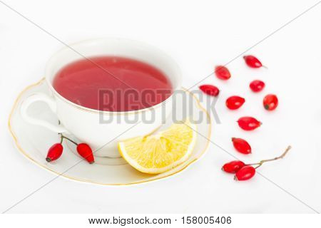 Cup of healthy rosehip tea with lemon slice on white background