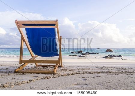 A blue deck chair invites to relax on this beautiful white beach in Ko Lipe, Thailand
