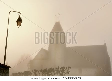church of a village and a lamppost in the fog