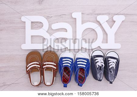 Different baby shoes and word BABY on wooden floor, top view
