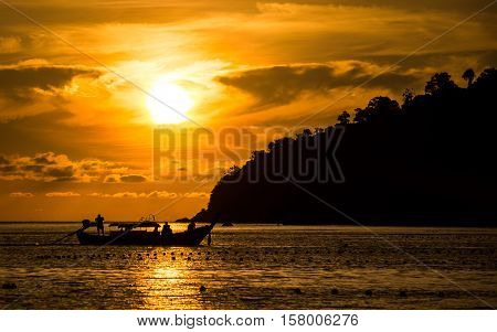 Sunset view from Pattaya beach in Ko Lipe, Thailand shows a longtail boat driving in front of the setting sun
