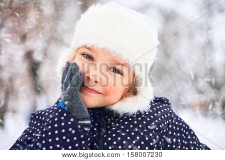 Portrait of a cute little girl in a snowy park during a snowfall.