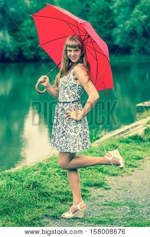 Beautiful young lady with red umbrella near the pond - retro style