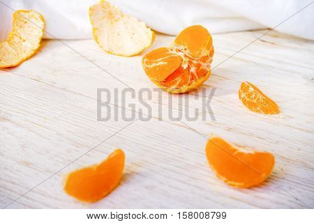 peeled tangerine on white boards close up