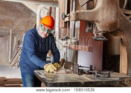 Senior carpenter with competence working on band saw