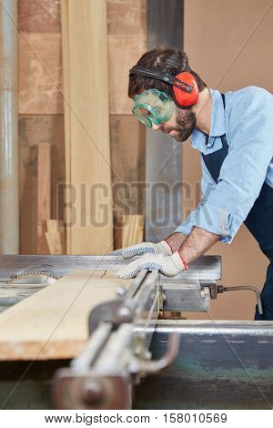 Artisan working with ear and eyes protection at carpentry workshop