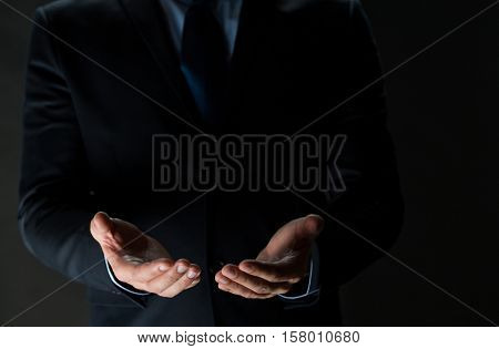 business, virtual reality, people and advertisement concept  - close up of businessman in suit holding something imaginary on palms of his hands