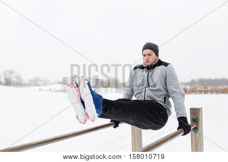 fitness, sport, exercising and people concept - young man doing abdominal exercise on parallel bars in winter