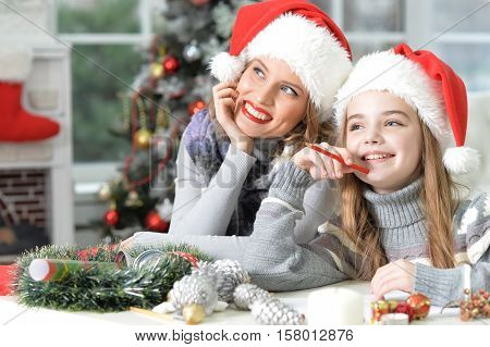 Portrait of mother and preteen daughter preparing for Christmas writing letter