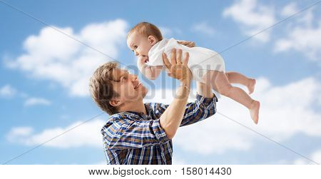 family, fatherhood and parenthood concept - happy smiling young father with little baby over blue sky and clouds background