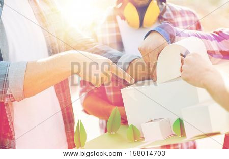 building, construction, teamwork and people concept - close up of builders hands with paper house model or layout outdoors