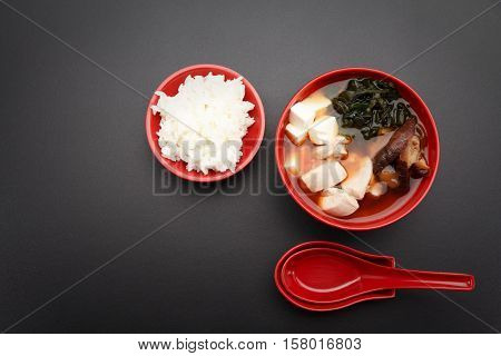 Japanese Miso Soup And Rice On A Red Bowl And Spoon On The Table.