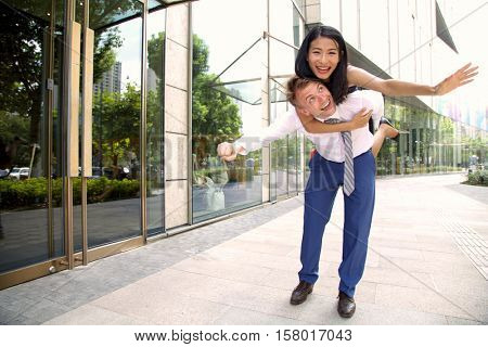 Multi ethnic inter racial couple lovingly having a piggy back ride in the city