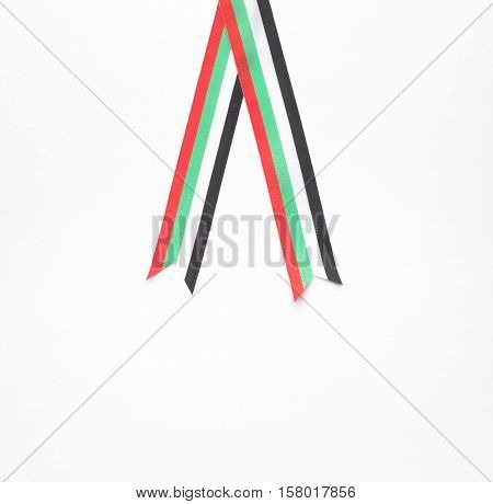 A piece of striped ribbon with colors of national flag of UAE. Awards and accolades motif.